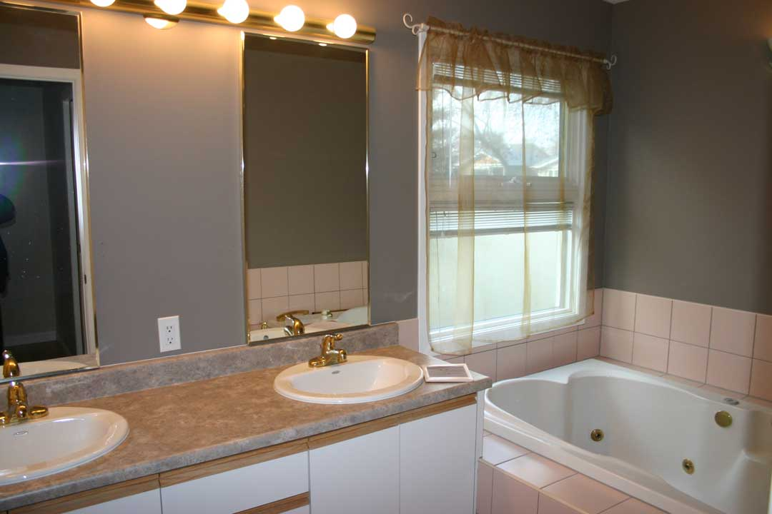 Before renovation - a 4-piece bathroom with double sinks and a jetted tub